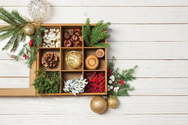 Natürliche weihnachtsdekorationen auf weißem hölzernem hintergrund