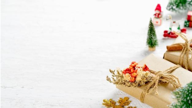 Natürliche weihnachtsgeschenkbox mit kiefer und weihnachten spielt dekoration