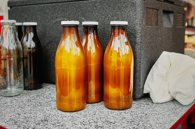 Natürliche ziegenmilch in der braunen flasche des kraftpapiers an einem landwirtmarkt. nützliches und gesundes essen