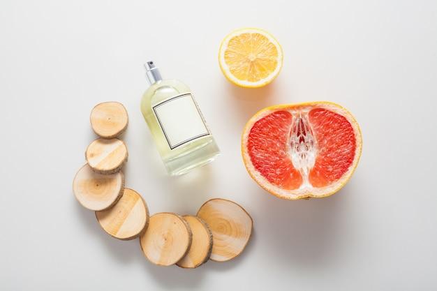 Natürliche zutaten für einen holzigen zitrusduft, eine flasche öl oder parfüm an einer wand aus grapefruit, zitrone und holz. das konzept von parfums und aromatherapie, körperpflege, natürlichen ölen.