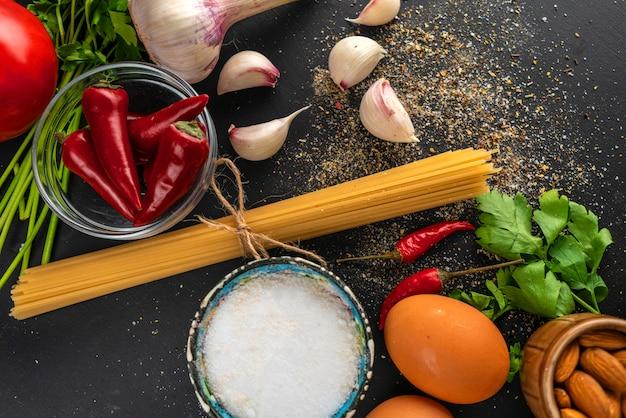 Natürliche zutaten zum kochen von nudeln, rohe spaghetti mit einem seil, salz und pfeffer auf den tischen