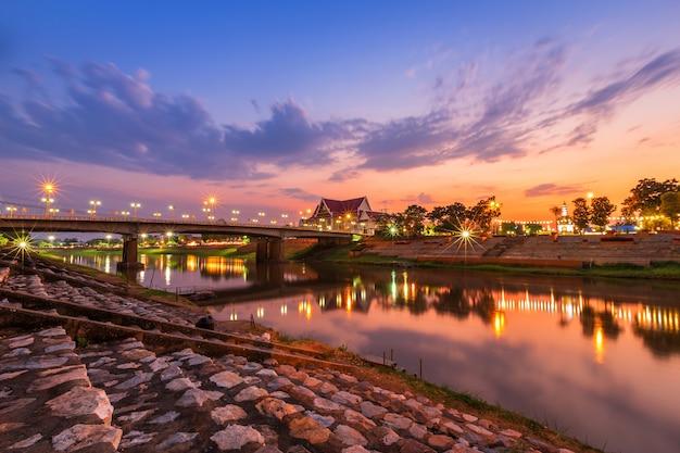 Natürlicher abend bei blick auf den nan river und die naresuan bridge im park