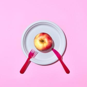 Natürlicher bio-apfel auf einem einweg-teller serviert mit plastikmesser und gabel auf einem rosa hintergrund mit kopienraum. draufsicht.