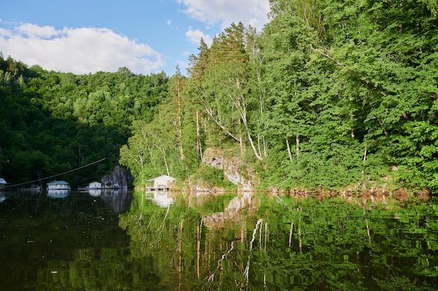 Natürlicher blick auf grüne felder im vordergrund und berge von klippen und hügeln an einem sonnigen sommertag.