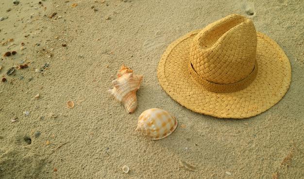 Natürlicher brauner strohhut mit schönen natürlichen muscheln auf dem sandstrand von thailand
