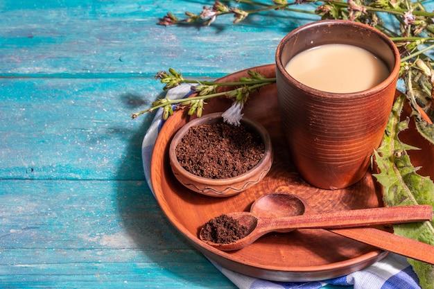 Natürlicher chicorée-kaffee mit frischen blumen und pulver. koffeinfreies getränk in einem keramikglas. alternativer ersatz für kaffee, koffein. türkisfarbener holzhintergrund, platz für text