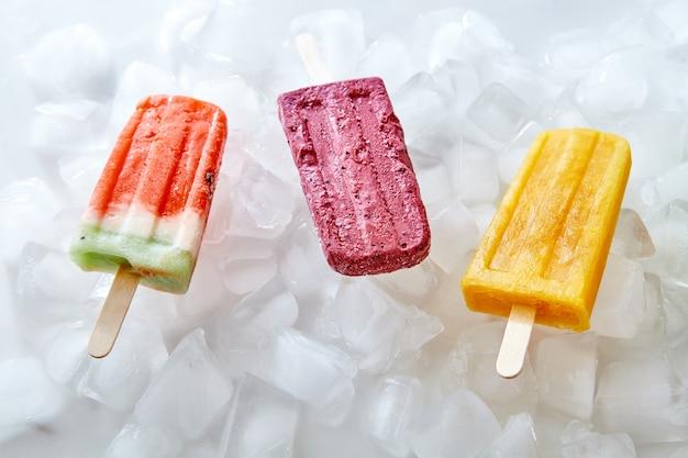 Natürlicher gefrorener fruchtsaftlutscher auf einem stock auf eiswürfeln