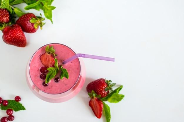 Natürlicher gesunder smoothie mit erdbeerorganischer draufsichtebenenlage des joghurts und der minze
