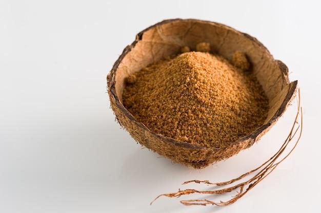 Natürlicher granulierter kokosnusszucker in einer kokosnussschale