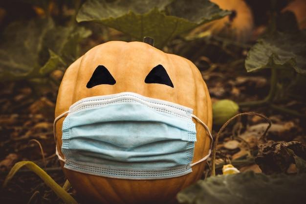 Natürlicher halloween-kürbis, maskiert von der coronavirus-pandemie