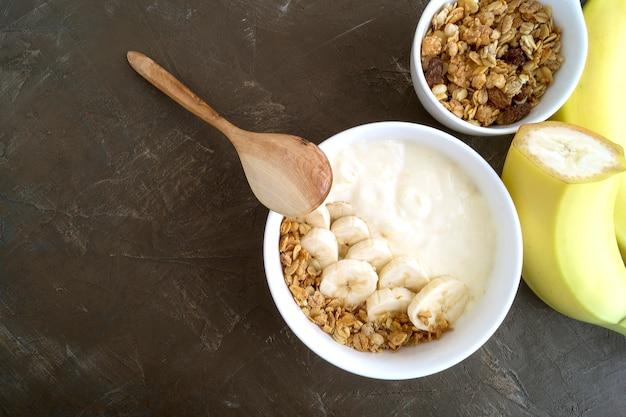 Natürlicher hausgemachter joghurt mit müsli und banane.