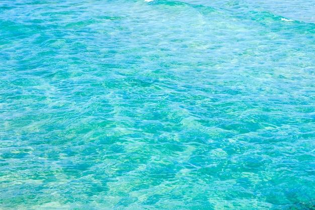 Natürlicher hintergrund der fließenden wasseroberfläche des blauen meeres mit wellen und etwas bodenansicht.