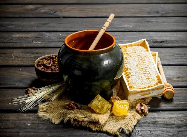 Natürlicher honig in einem topf mit einem löffel. auf einem holz.