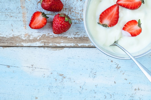 Natürlicher joghurt und erdbeerfrucht auf dem hölzernen hintergrund