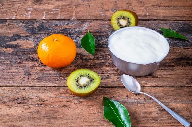 Natürlicher joghurt und frucht auf holztisch