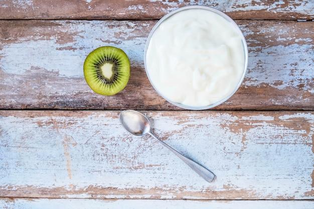 Natürlicher joghurt und kiwi auf holztisch