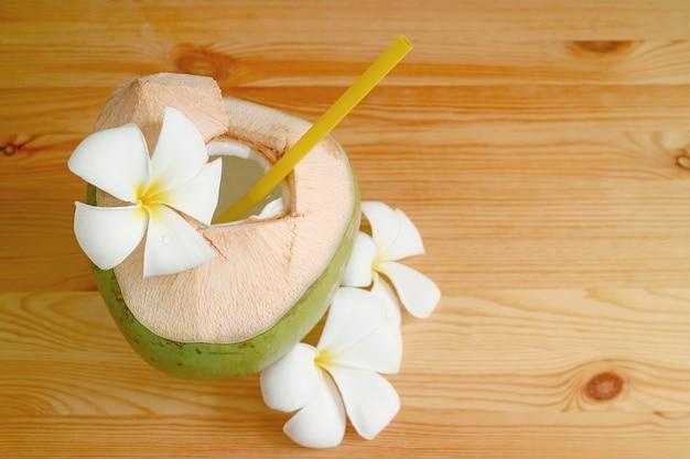 Natürlicher junger kokossaft und fruchtfleisch in seiner schale mit plumeria-blüten auf einem holztisch