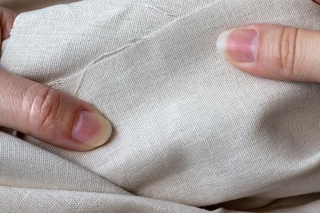 Natürlicher leinenstoff in weiblichen händen.