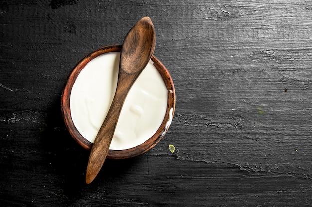 Natürlicher milchjoghurt in einer schüssel mit einem löffel. auf der schwarzen tafel.