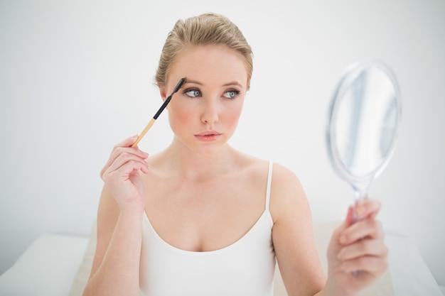 Natürlicher ruhiger blonder haltener spiegel und anwendung der augenbrauenbürste