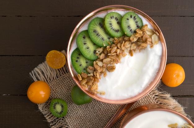 Natürlicher selbst gemachter joghurt mit bodenkirsche auf einem holztisch.