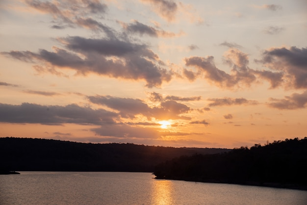 Natürlicher sonnenuntergang-sonnenaufgang über feld mit berg