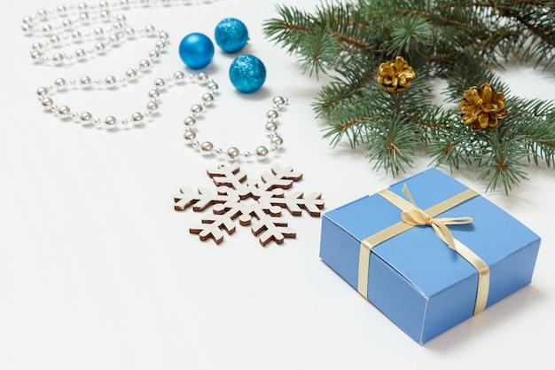 Natürlicher tannenzweig mit zapfen, einer geschenkbox und anderem weihnachtsschmuck auf weißem hintergrund