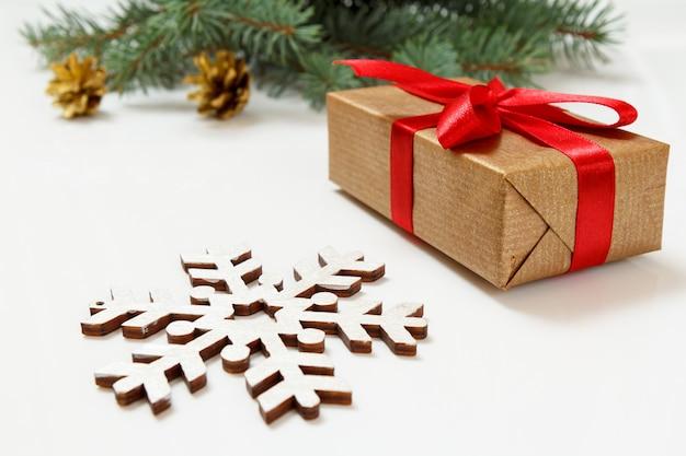 Natürlicher tannenzweig mit zapfen, einer geschenkbox und anderen weihnachtsschmuck auf dem weißen hintergrund.