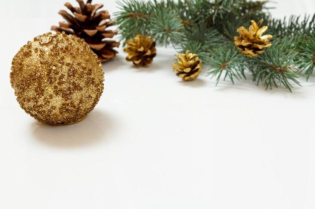 Natürlicher tannenzweig mit zapfen und weihnachtsschmuck auf weißem hintergrund