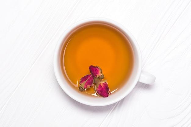 Natürlicher tee aus knospen einer rose in einer weißen tasse