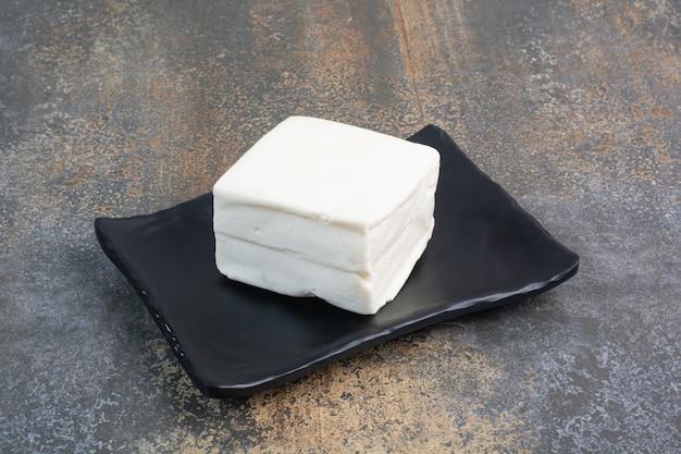 Natürlicher weißer käse auf schwarzem teller.