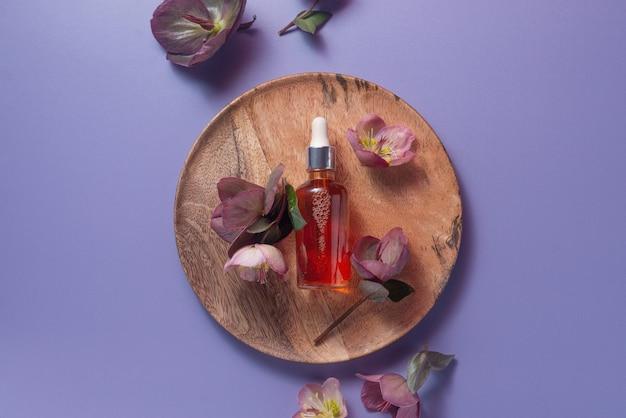 Natürliches bio-vitamin-c-serum auf einer holzplatte, umgeben von blumen auf pastellviolettem hintergrund