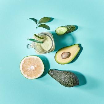 Natürliches frisch gepflücktes gemüse und obst für die zubereitung eines gesunden vegetarischen smoothie in einem glas auf grün. flach liegen.