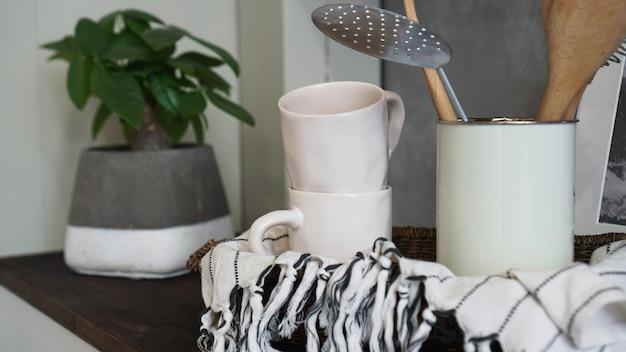 Natürliches geschirr auf holzuntergrund. keramikschale und tassen in neutralen tönen im skandinavischen stil.