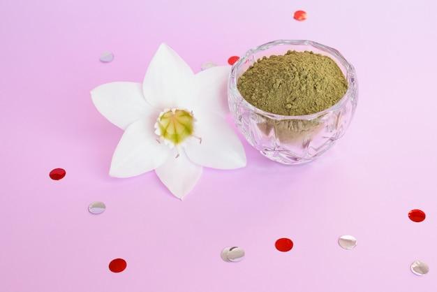 Natürliches henna-pulver und pflanzenschmerle auf einer rosa oberfläche. konzept weibliche schönheit und kosmetologie. augenbrauen- und haarfärbung.