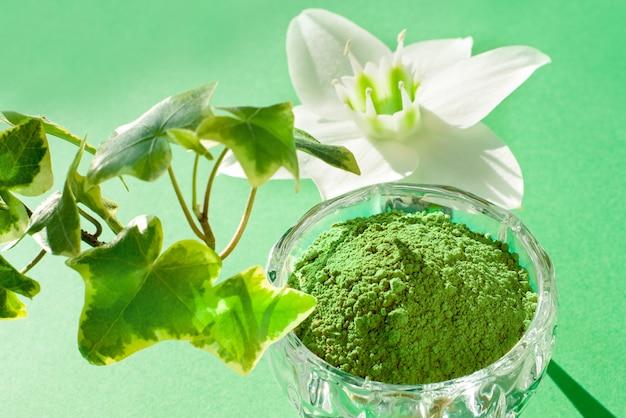 Natürliches henna-pulver und pflanzenschmerle auf grünem grund. konzept weibliche schönheit und kosmetologie. augenbrauen- und haarfärbung.
