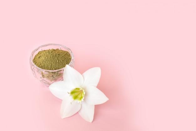 Natürliches hennapulver und weiße blume in einer weiblichen hand auf einem rosa hintergrund. konzept weibliche schönheit und kosmetologie. augenbrauen- und haarfärbung.