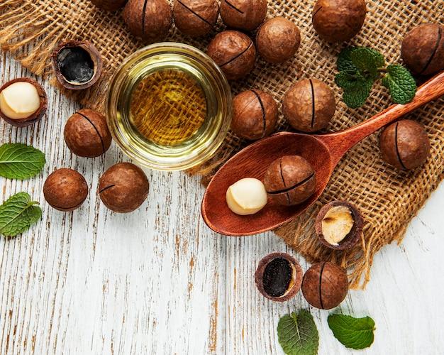 Natürliches macadamiaöl und macadamianüsse auf holzbrett