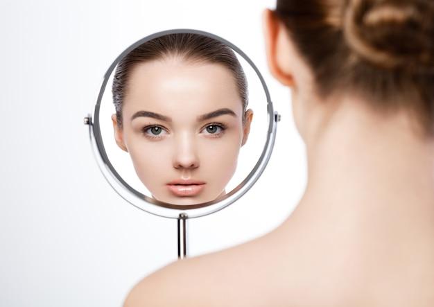 Natürliches make-up des schönheitsmädchens, das in der spiegelreflexion auf weiß schaut