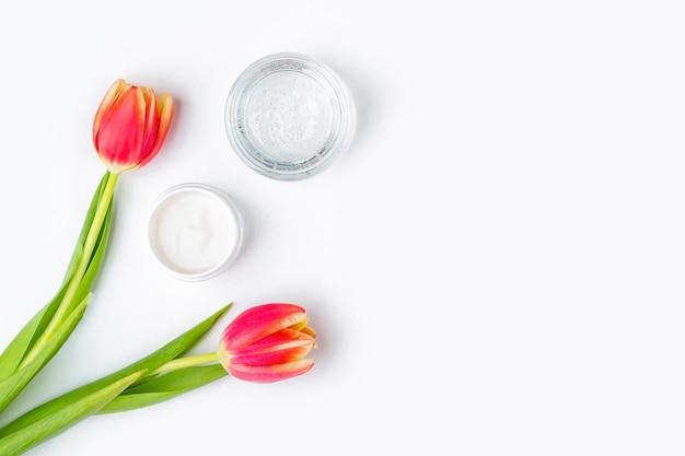 Natürliches organisches hausgemachtes kosmetikkonzept. hautpflege-, heil- und schönheitsprodukte: behälter mit creme und serum unter den frühlingsrottulpenblüten auf weißem hintergrund. flach legen, platz für text kopieren