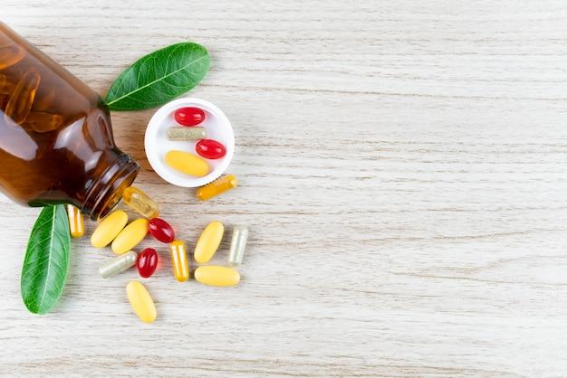 Natürliches organisches vitamin und ergänzungen, blatt im mörser auf hölzernem hintergrund-, medizin- und drogenkonzept
