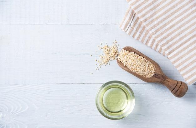 Natürliches pflanzenöl aus sesamsamen in einer klaren schüssel auf dem holzhintergrund. diätetische gesunde nahrung. draufsicht und kopierbereich