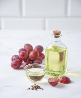 Natürliches pflanzenöl aus traubenkernen in einer klaren flasche auf dem küchentisch. diätetische gesunde nahrung. vorderansicht