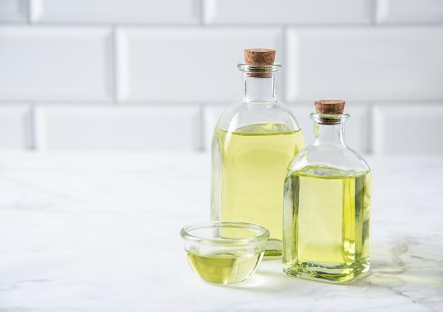 Natürliches pflanzenöl in einer klaren flasche auf dem küchentisch. diätetische gesunde nahrung. vorderansicht und kopierbereich
