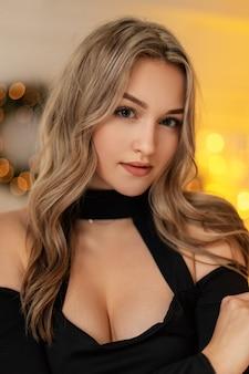 Natürliches porträt einer schönen jungen stilvollen frau mit einer frisur in einem modischen schwarzen kleid auf einem hintergrund von gelben bokeh-lichtern im innenbereich. weihnachtsfeier und feiertage