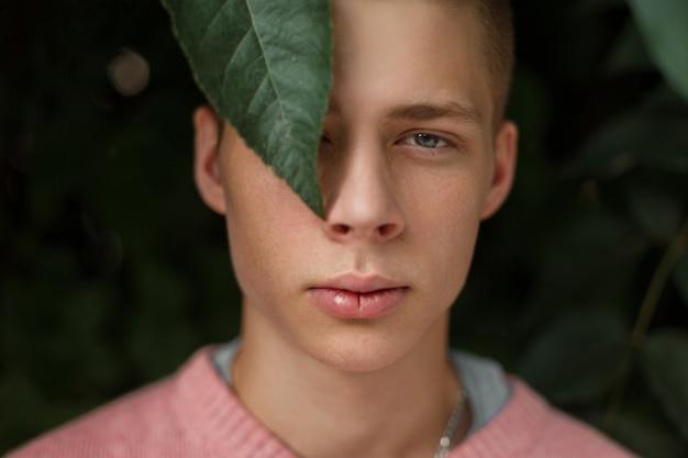 Natürliches porträt eines gutaussehenden mannes mit sommersprossen nahe grünen blättern