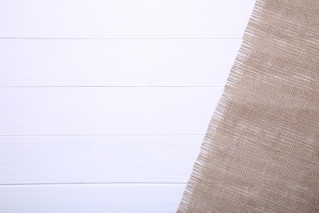 Natürliches sackleinen auf einem weißen hölzernen hintergrund.