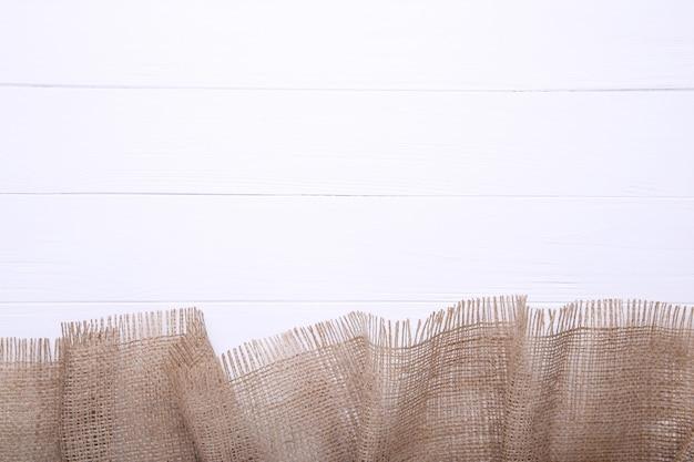 Natürliches sackleinen auf weißem hölzernem hintergrund.