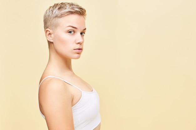Natürliches schönheits-, jugend-, gesundheits- und stilkonzept. seitenbild der attraktiven blauäugigen blonden jungen europäischen frau mit stilvoller pixie-frisur mit sicherem gesichtsausdruck