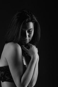 Natürliches schönheitskonzept. sexy körper der jungen attraktiven frau gegen dunkelheit
